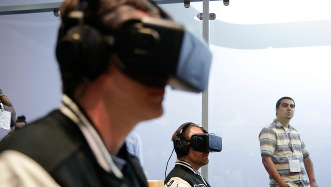 In this June 10, 2014 file photo, show attendees play a video game with Oculus Rift virtual reality headsets at the Electronic Entertainment Expo, in Los Angeles. Oculus, the virtual reality company acquired by Facebook earlier this year for $2 billion, is holding its first-ever developers conference and is expected to discuss the much-anticipated release of its VR headset for consumers. The two-day Oculus Connect conference begins Friday, Sept. 19, 2014. (AP Photo/Jae C. Hong, file)