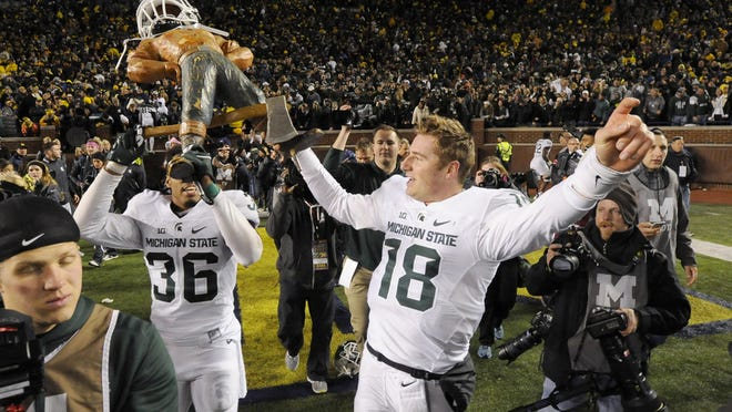Michigan State's Arjen Colquhoun, left, and Connor Cook carry the Paul Bunyan trophy in Michigan Stadium after the Spartans' victory Saturday night.