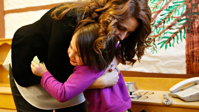 Substitute teacher Tabatha Peters, back, of West York Borough, receives a hug from student Lexi Mast, 4, during Community Progress Council's Head Start in York City, Friday, Dec. 15, 2016. Dawn J. Sagert photo