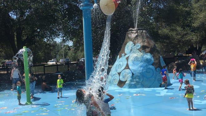 A bucket dumps water on children Tuesday at the Fantasy Fountain water-spray park at Kids Kingdom.