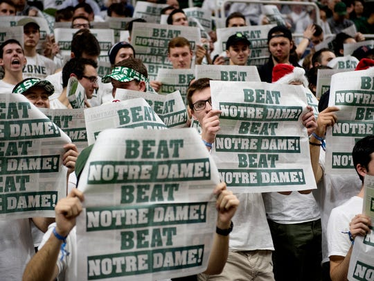 Michigan State fans hold up newspapers while Notre Dame's team is introduced before the start of MSU's game against the Fighting Irish on Thursday, Nov. 30, 2017, at the Breslin Center.