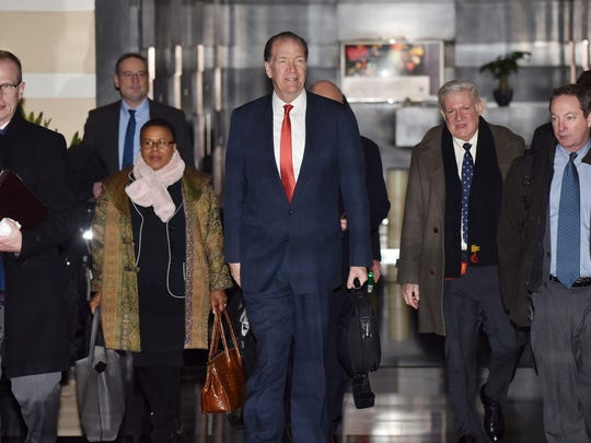"US Undersecretary for International Affairs David Malpass (C) leaves a hotel with members of a negotiation team on the way to trade talks in Beijing on February 12, 2019. - Negotiators headed to a second day of trade talks on February 12, hoping to reach a deal before the March 1 deadline set by Donald Trump as the IMF warned of a possible global economic ""storm""."