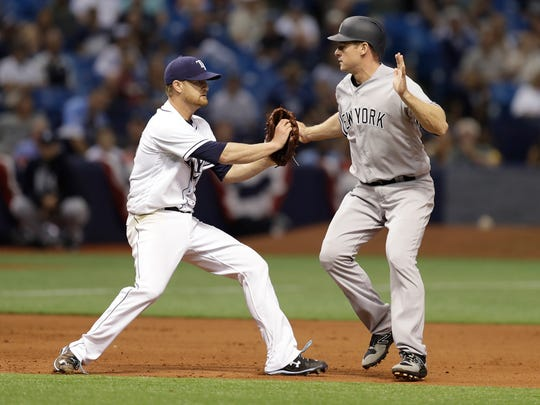 Rays starting pitcher Alex Cobb, left, tags out Yankees' Chase Headley after he was caught in a rundown on a fielder's choice by Aaron Judge during the fifth inning of a baseball game Wednesday, April 5, 2017, in St. Petersburg, Fla.