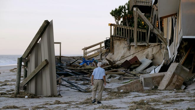 H.V. Bailey looks at damage to a neighbor's home at Ponte Vedra Beach, Fla., on Saturday, after Hurricane Matthew passed through on Friday.