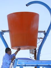 Carlos Elizondo of the city of El Paso Parks and Recreation Aquatics Department puts the plug in the giant dump bucket at the splash pad at Marty Robbins Park in April.