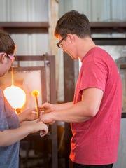 Instructor Devon Murphy helps students create glass