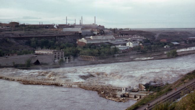 Floodwaters rush through Black Eagle Dam in June 1964.