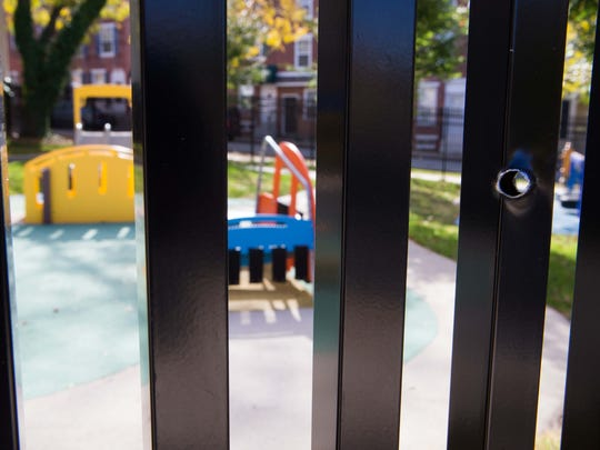 Bullet holes can be seen all around the black metal fence, the only barrier to the children's playground at the West Center City Early Learning Center at 600 N. Madison Street in Wilmington which is moving out of the area due to all the gun violence.