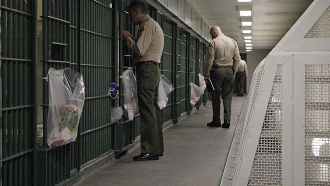 In this 2012 file photo, Los Angeles County Sheriff's deputies inspect a cell block at the Men's Central Jail in downtown Los Angeles.