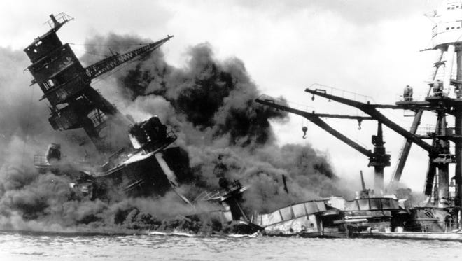 In this  Dec. 7, 1941 file picture, the battleship USS Arizona belches smoke as it topples over into the sea during a Japanese surprise attack on Pearl Harbor, Hawaii.