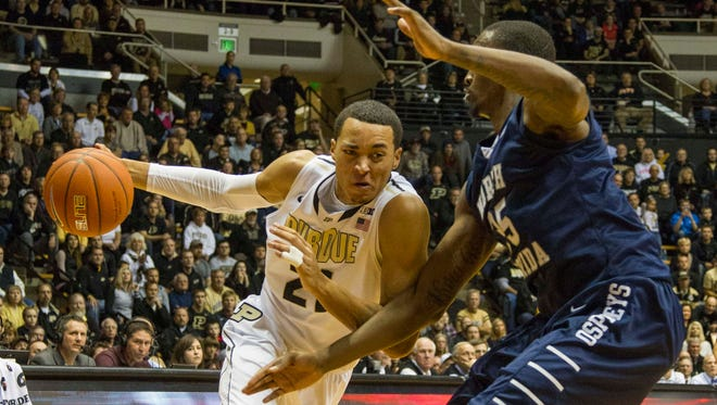 Purdue Boilermakers guard Kendall Stephens (21) dribbles the ball in on North Florida Ospreys forward Chris Davenport (35) in the second half of the game at Mackey Arena. The North Florida Ospreys beat the Purdue Boilermakers 73-70.