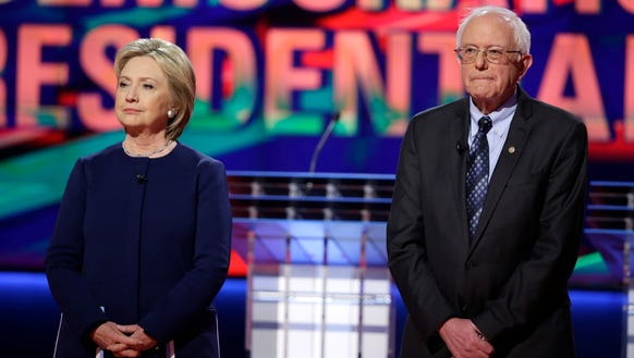 Hillary Clinton and Bernie Sanders stand on stage before