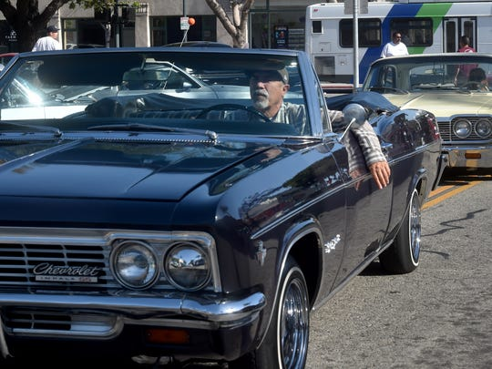 Rufino Esquivel drives his 1966 Chevy Impala Super Sport looking for a place to park along A Street in Downtown Oxnard on June 8 for the city's Cruise Night event.