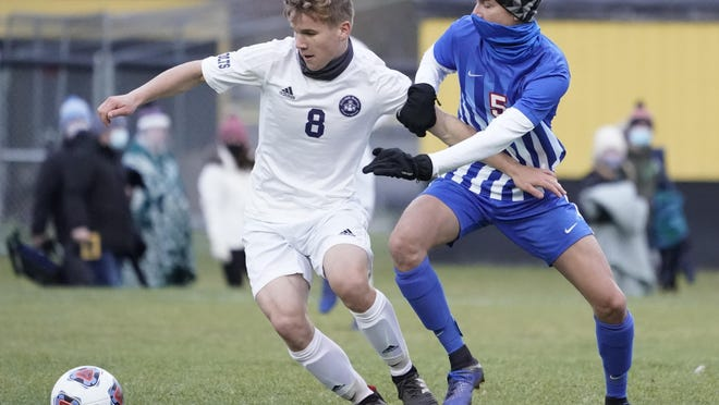 Luke Brady (8) of Hillsdale Academy and LCS' Brennan Griffith (5) jostle for control of the ball during Friday's Division 4 regional final soccer match. Photo: Mike Dickie