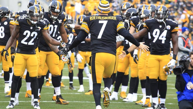 Dec 21, 2014; Pittsburgh, PA, USA; Pittsburgh Steelers quarterback Ben Roethlisberger (7) is greeted by teammates as he takes the field against the Kansas City Chiefs during the first quarter at Heinz Field.