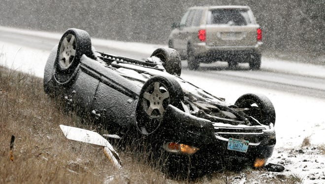 An overturn vehicle rests on the shoulder of a snow-covered U.S. 522 near Gainesboro, Va.,  Friday, Jan. 22, 2016.  There no injuries in the accident. A blizzard menacing the Eastern United States started dumping snow in Virginia, Tennessee and other parts of the South on Friday as millions of people in the storm's path prepared for icy roads, possible power outages and other treacherous conditions. (Scott Mason/The Winchester Star via AP) MANDATORY CREDIT