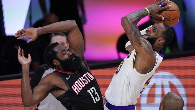 Los Angeles Lakers' LeBron James, right, shoots over Houston Rockets' James Harden (13) on Tuesday in Lake Buena Vista, Fla.