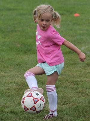 Eva Schroeder, 5, of Marshfield partcipates in a soccer drill at the Northridge Church Mega Sports Camp in Marshfield, Monday, June 29, 2015.