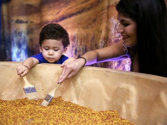 Maverick Rodriguez and his mother, Danielle, dig for dinosaur bones during the Discover the Dinosaurs event at Foster Communications Coliseum on Saturday.