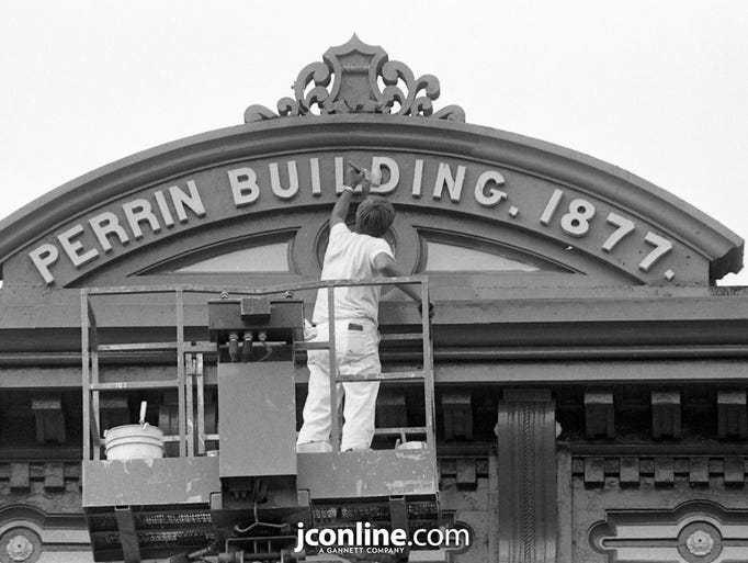 Larry Kelley of Wells Painting and Decorating Inc. touches up the lettering atop the Perrin Building on Main Street in downtown Lafayette. Kelley and partner Jesse Freels started painting the metal and wood front of the four-story building and expected to finish the job in about a week. Photo taken Aug. 28, 1984.