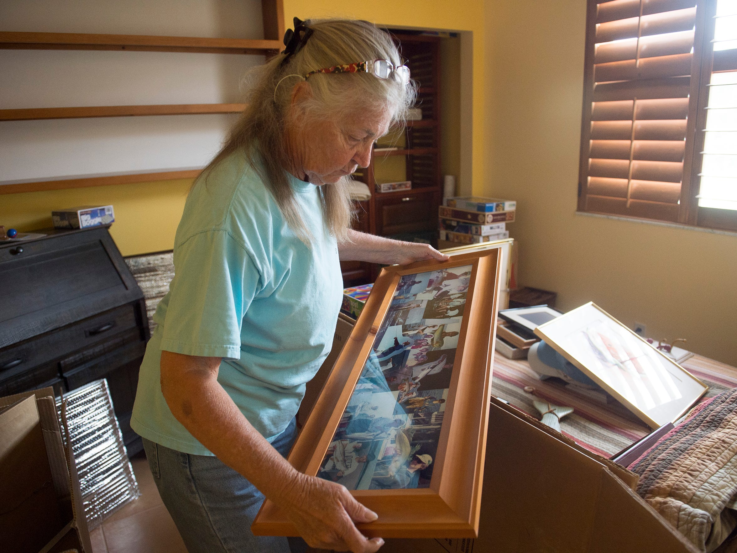 "Marcia Foosaner, a retired fishing guide, observes old images of her fishing with relatives and clients May 29 at her home in Palm City. ""I've got tons of these. They're everywhere. And they'll move, they'll go to the new house and I'll be able to look at them there and enjoy them,"" Foosaner said, as she continued packing for her relocation Lake Placid for cleaner water."