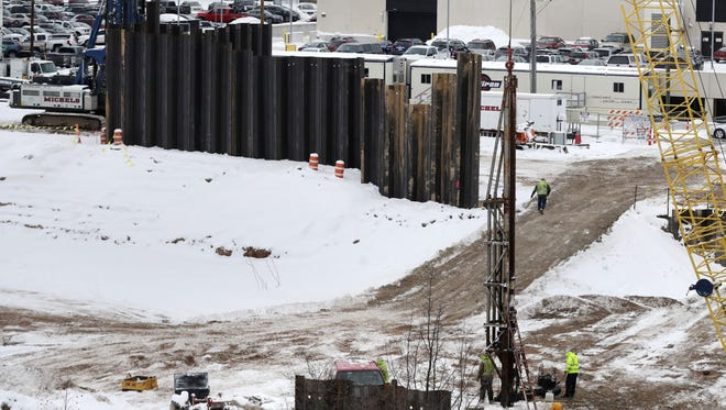 Contractors drive steel sheet piling into the ground as part of the construction of the Fox Cities Exhibition Center in Appleton.