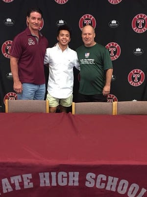 Tate High senior Jacob Cochran, center, with Tate coach Reggie Allen, left , and Northern Michigan/U.S. Olympic Training Center coach Rob Hermann and Cochran's recent signing event at Tate HIgh.