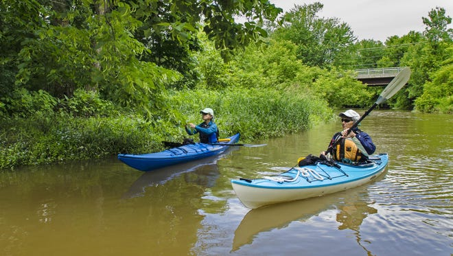 Kathy Frank, right, and Margy Holden paddle the LaPlatte River in Shelburne in mid-June, 2015.  A salt transfer station is being constructed on the bluff that rises to the right of the photograph.
