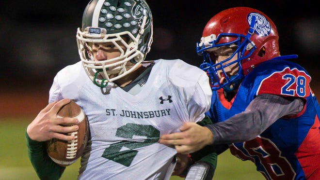 St. Johnsbury's Jake Cady, left, tries to break free of Hartford's Kody Rhodes during last year's Division I high school football state championship in Rutland. The teams meet in a rematch on Saturday.