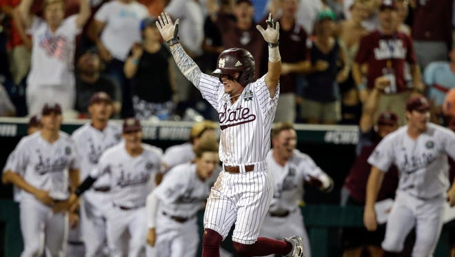 Mississippi State's Hunter Stovall, center, celebrates as he runs to home plate for the winning run against Washington on a single by Luke Alexander in the ninth inning of an NCAA College World Series baseball game in Omaha, Neb., Saturday, June 16, 2018. (AP Photo/Nati Harnik)