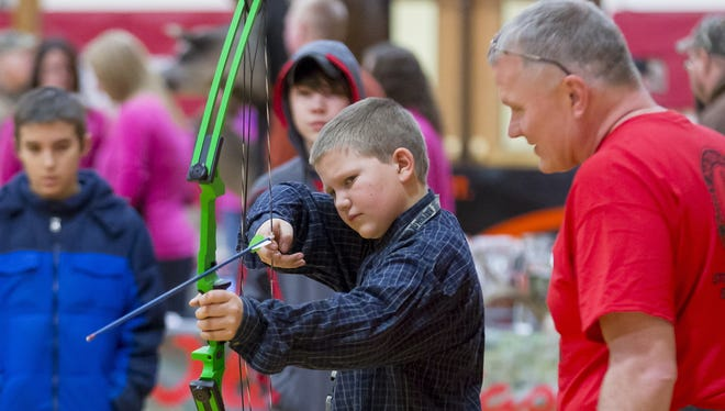 Ryan Morse, left, of Spencer, demonstrates the use of a Genesis compound bow during the 2014 Spencer-Van Etten Sportsman Day. Looking on is George Lampila, a member of the Spencer-Van Etten Sportsman's Club.