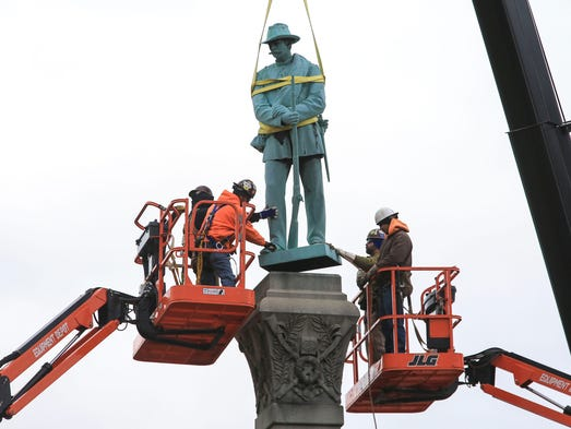 Workers keep a hand on the Confederate soldier as a