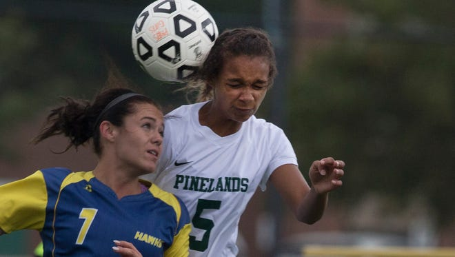 Manchester's Olivia Hand watches as Pinelands' Madison Doughty heads ball during first half action. Manchester Girls Soccer vs Pinelands in Tuckerton, NJ on October 4, 2016