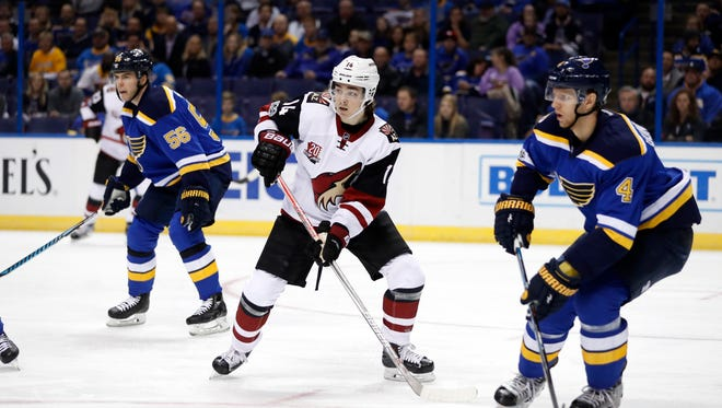 Arizona Coyotes' Clayton Keller, center, skates between St. Louis Blues' Magnus Paajarvi (56) and Carl Gunnarsson, of Sweden, during the first period of an NHL hockey game Monday, March 27, 2017, in St. Louis.