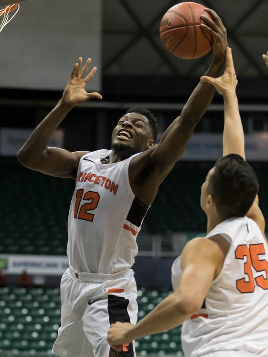 Princeton guard Myles Stephens (12) grabs a rebound has his teammate forward Alec Brennan (35) looks on during the first half of an NCAA college basketball game at the Diamond Head Classic tournament, Friday, Dec. 22, 2017, in Honolulu. (AP Photo/Eugene Tanner)