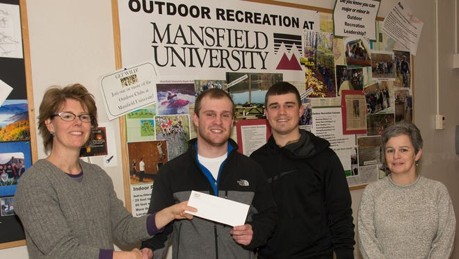 From left, board member Lilace Guignard presents the grant check from Mill Cove to Mansfield University students Matthew Oldroyd and Clayton Schucker, both of Troy, and assistant professor Linda Kennedy.