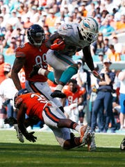 Miami Dolphins running back Frank Gore (21) jumps over Chicago Bears strong safety Adrian Amos (38), during the second half of an NFL football game, Sunday, Oct. 14, 2018, in Miami Gardens, Fla. (AP Photo/Joel Auerbach)