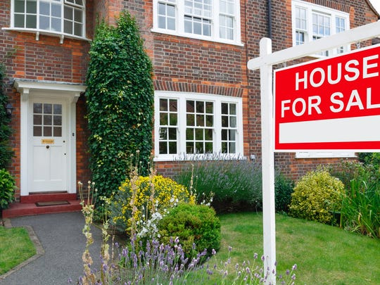 Home with HOUSE FOR SALE sign on front yard.