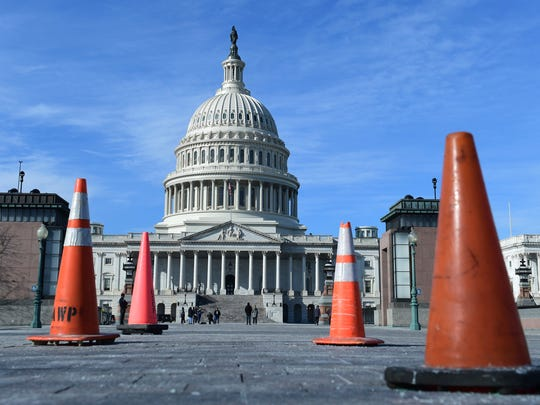 Construction cones used to cover walkway flaws, stand along the sidewalk on Capitol Hill in Washington, Friday, Jan. 19, 2018. On the edge of a government shutdown, a divided House voted late Thursday to keep the government open past a Friday deadline — setting up an eleventh-hour standoff in the Senate, where Democrats have vowed to kill the measure. (AP Photo/Susan Walsh)