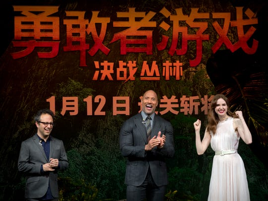 'Jumanji: Welcome to the Jungle' director Jake Kasdan, from left, Dwayne Johnson and Karen Gillan laugh during a news conference for the movie in Beijing.