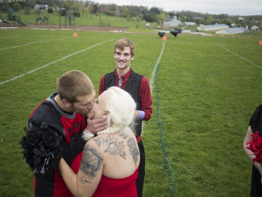 Cody's twin brother, Zach Klinefelter, center back, and maid of honor Brittney Reese, far right, look on as Cody Klinefelter and Beth Ford kiss during the ceremony. Cody Klinefelter, 25, and Beth Ford, 36, are married before friends, family and Cody's Hanover Rhinos football teammates at Manheim Adventure Park in Glenville prior to a Rhinos' game, Saturday, April 23, 2016.