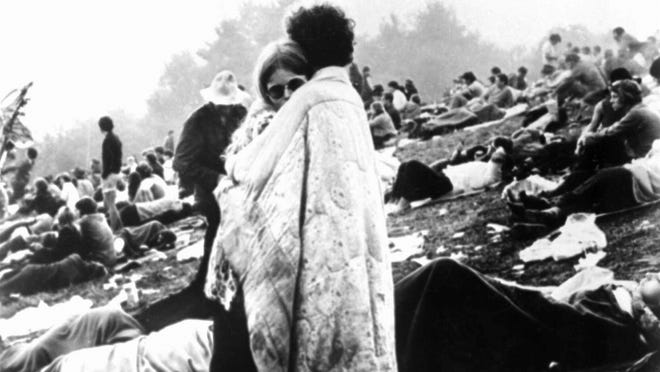 A couple embrace on a muddy hillside in Bethel, N.Y. during the Woodstock Music and Art Fair in August 1969.