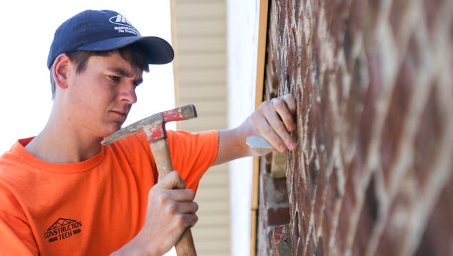 """Austin Scott, a Prosser Career Education Center student, works on finishing a brick window sill on a house in the Builder's Ridge subdivison in New Albany. The subdivision belongs to Prosser and the school uses the hands-on opportunities for its students, looking to complete one home a year. """"I've always been fascinated by brick laying,"""" Scott, who took first in the state masonry competition, said. """"I've caught on to it and I've really liked it so far."""" March 21, 2016"""