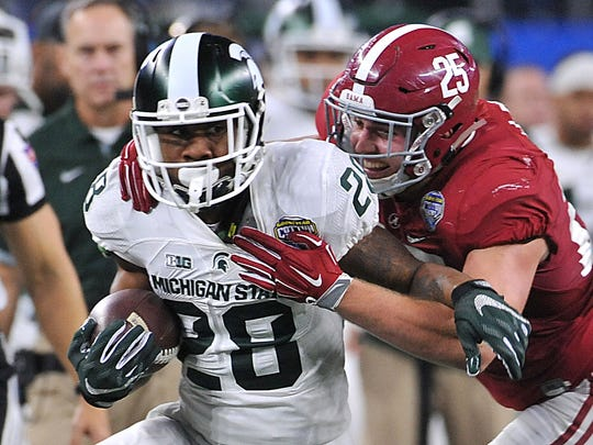 Michigan State's Madre London gets tackled by Dillon Lee as MSU falls to Alabama in the Cotton Bowl on Dec. 31, 2015.