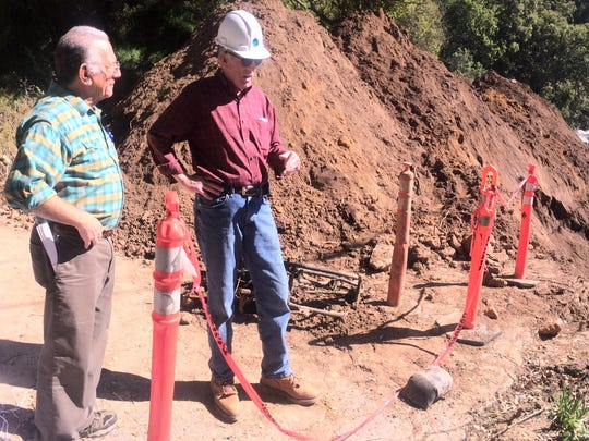 Supervisor John Phillips, right in the red shirt, surveys damage on Elkhorn Road earlier this month.