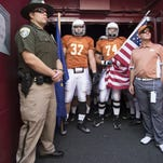 Montana defensive tackle Caleb Kidder (37), offensive lineman John Schmaing (74) and head coach Bob Stitt (right) get ready to lead the Grizzlies on the field before playing Northern Arizona a few weeks ago in Missoula.