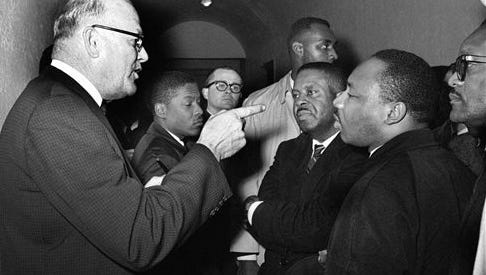 In this March 1, 1965, file photo, Registrar Carl Golson shakes a finger at Martin Luther King Jr. during a meeting at the courthouse in Hayneyville, Ala. King inquired about voter registration procedures but Golson told him that if he was not a prospective voter in Lowndes county, 'It's none of your business.' King visited two nearby counties after leading a voter registration drive in Selma.