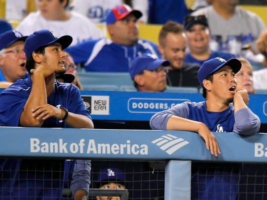 Los Angeles Dodgers' Yu Darvish, left, of Japan, and Kenta Maeda, of Japan, watch a ball hit by Arizona Diamondbacks' J.D. Martinez go out for a two-run home run during the ninth inning of a baseball game, Monday, Sept. 4, 2017, in Los Angeles. It was Martinez's fourth home run of the game. (AP Photo/Mark J. Terrill)