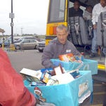 Food for Families volunteers unload a shipment of food goods from  Lawtell Head Start  Wednesday at the Opelousas Wal-Mart.