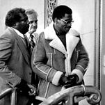 """In this Nov. 8, 1985, file photo, Rubin """"Hurricane"""" Carter (right), the former middleweight boxer, is escorted into federal court in Newark, N.J. Carter, who spent almost 20 years in jail after twice being convicted of a triple murder he denied committing, died at his home in Toronto on Sunday, according to long-time friend and co-accused John Artis. He was 76."""